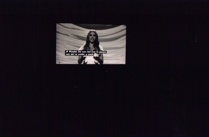 "black and white photograph of a television where eurovision is playing. there is a woman on the screen with subtitles ""Maybe we can not live in peace cos we are under a spell"""